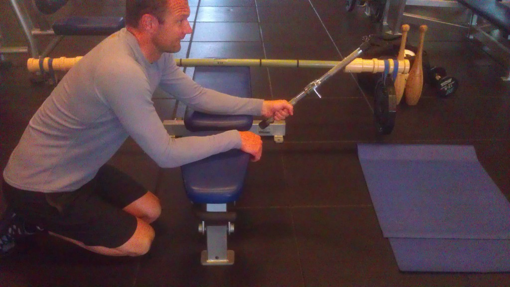 A kart racer training with a lat pull-down hand grip as a weight for wrist flexion/extension training
